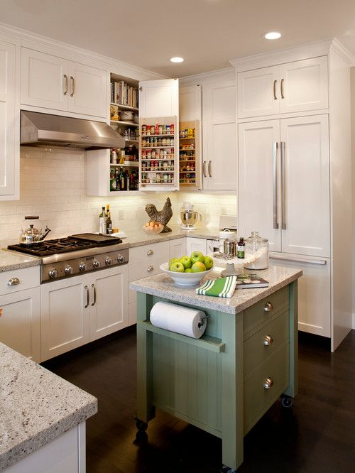 an elegant white kitchen with neutral stone countertops, chic furniture and handles and an olive green kitchen island on casters