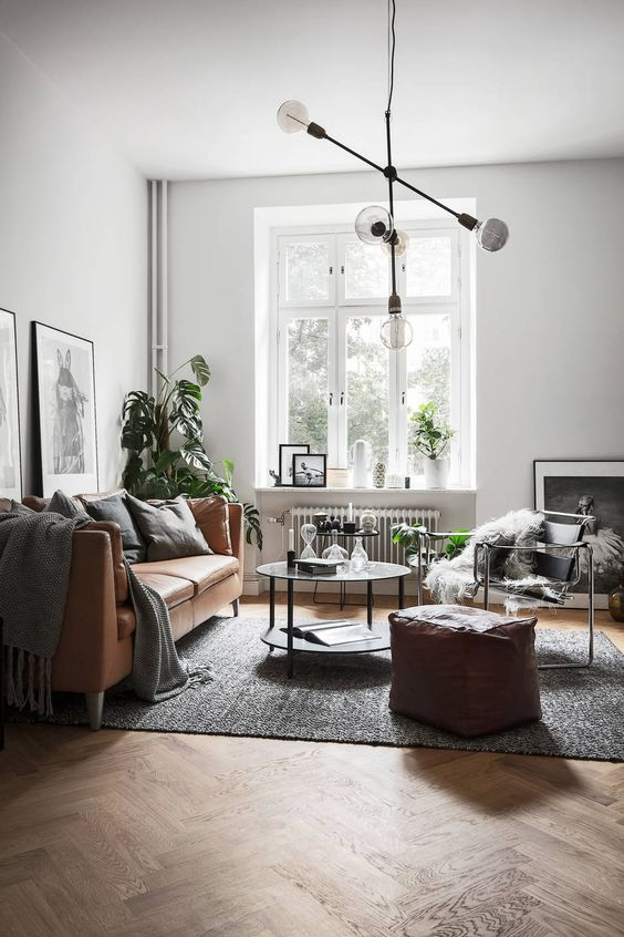 a Scandinavian space in a monochromatic color scheme, a tan leather Stockholm, round tables, black and white artworks and potted plants