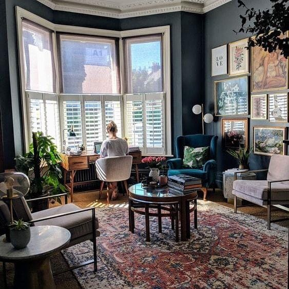 a bold maximalist living room with a working space in the bow window niche, pastel and neutral furniture and a bold gallery wall