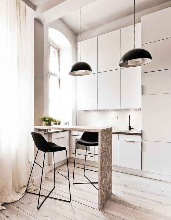 a tiny white kitchen with a raised breakfast bar counter and black stools plus black pendant lamps is super chic