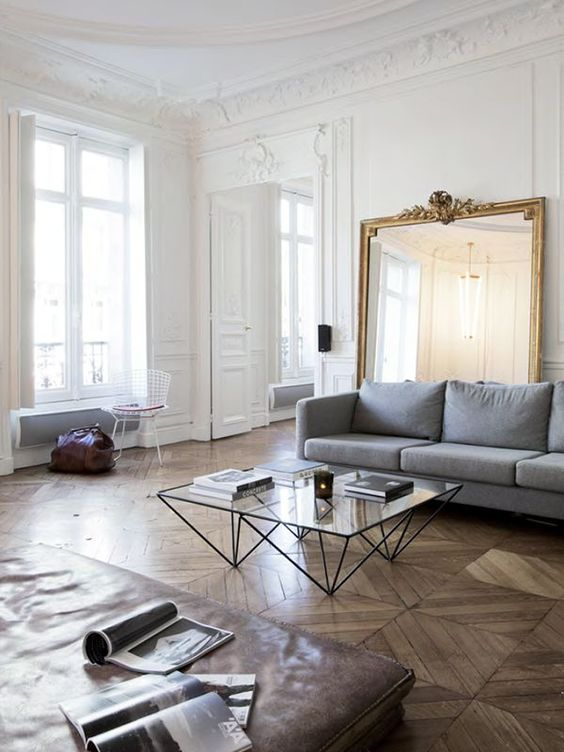 08 an exquisite Parisian living room with a grey sofa, a leather couch, a glass table and an oversized mirror in a gilded frame