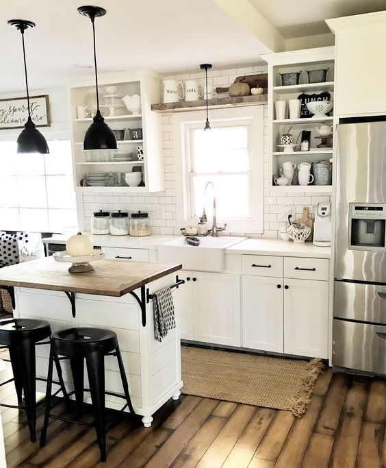 an inspiring white retro kitchen with subway tiles, black fixtures, a small kitchen island and black stools and pendant lamps
