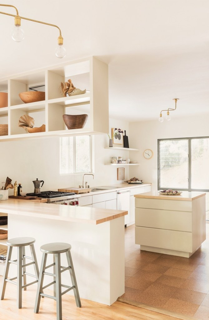 a beautiful and airy white kitchen with sleek cabinets, floating shelves and a suspended shelf, a small kitchen island that matches