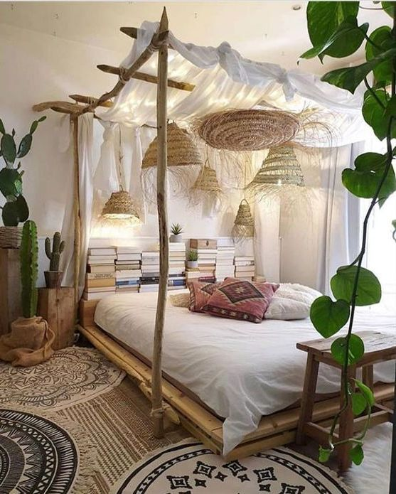 a boho bedroom with a canopy bed styled with curtains, lights, wicker pendant lamps, neutral bedding, stacked books and potted plants