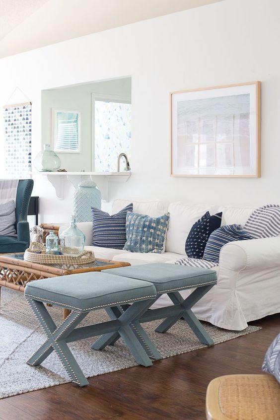 a coastal living room with a white Ektorp sofa, a rattan coffee table, blue stools and coastal artworks