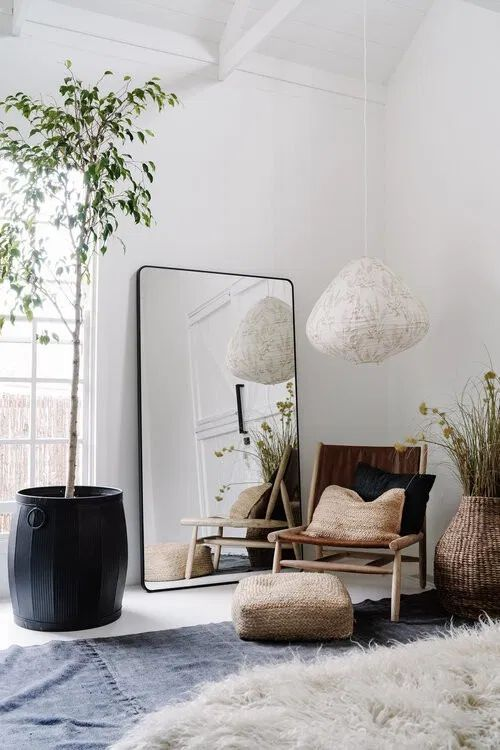09 a stylish boho nook with a wooden chair and jute pillows, an oversized mirror in a sleek black frame and some potted plants