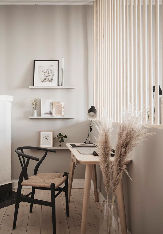 10 a Nordic working space with a sleek blonde wood desk, a woven chair, floating shelves, artworks, a black table lamp is wow