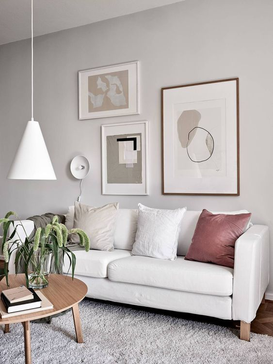a beautiful neutral living room with a lovely gallery wall, a neutral Stockholm sofa, a pendant lamp and some greenery in a vase