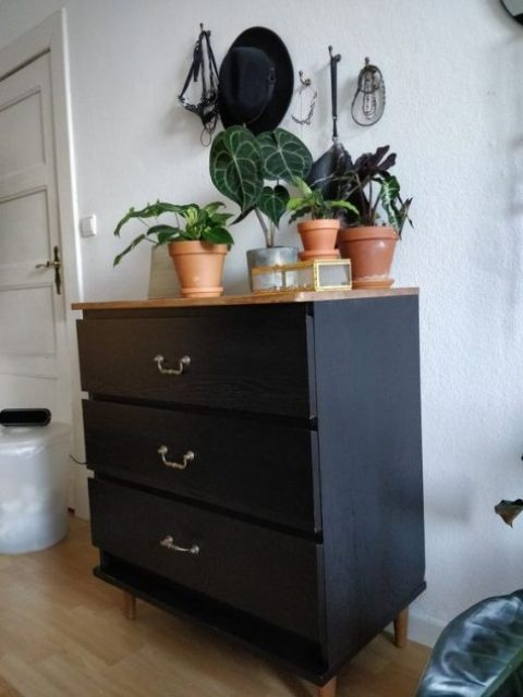 10 a black IKEA Malm dresser with refined metal handles and a light-stained wooden top is a stylish mid-century modern idea