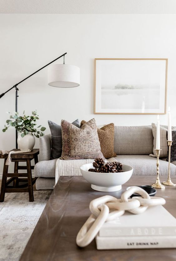 10 a chic neutral living room with a grey sofa, printed pillows, a low coffee table, a floor lamp and greenery in a vase