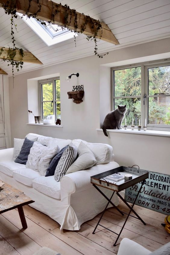 a laid-back farmhouse space with a white Ektorp, wooden beams with greenery, a metal tray table and a low wooden one