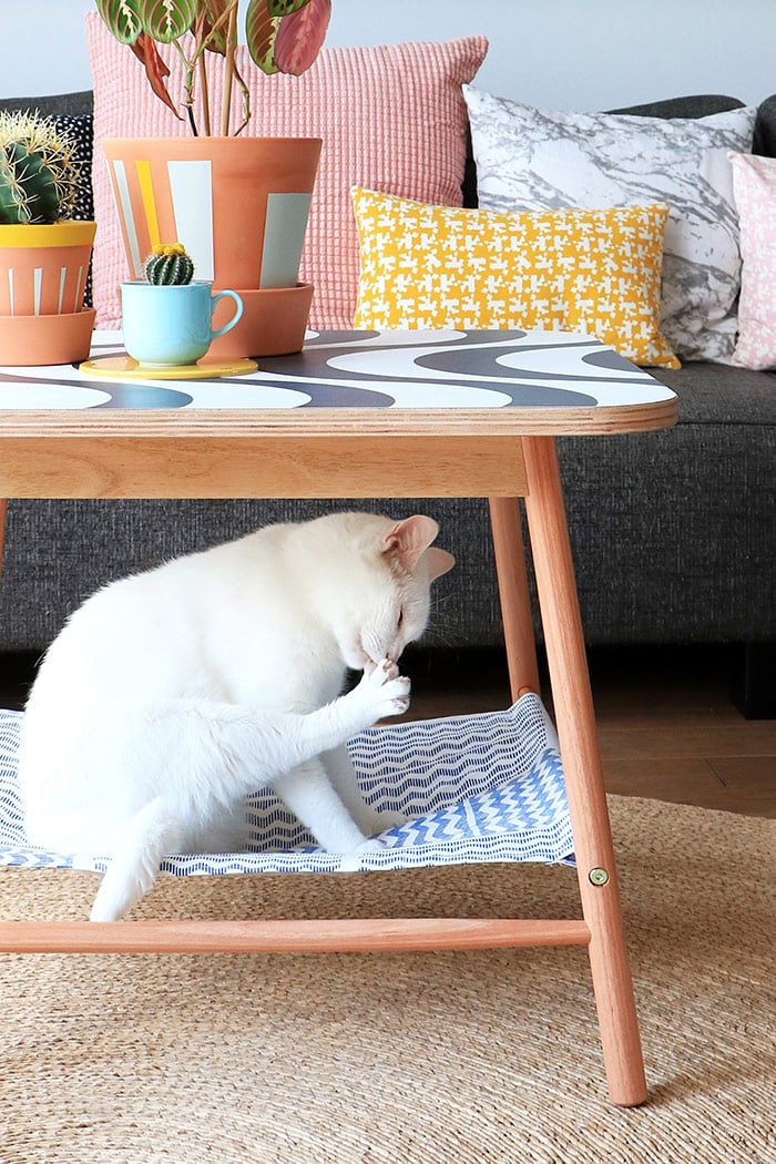 a modern IKEA coffee table hack with a painted tabletop and a cat hammock attached under it is a masterpiece to let your cat be everywhere with you