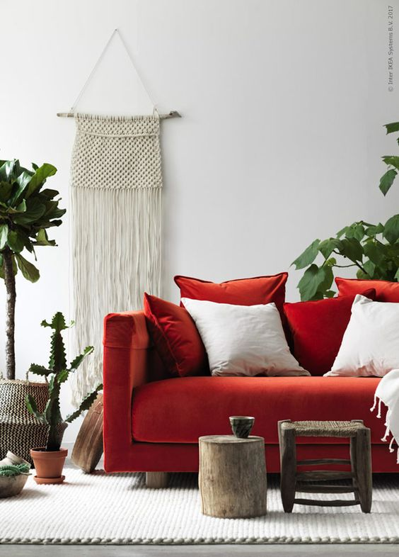 a boho living room with a fiery red Stockholm sofa, a wooden stool and tree stump, potted plants and cacti and a macrame hanging