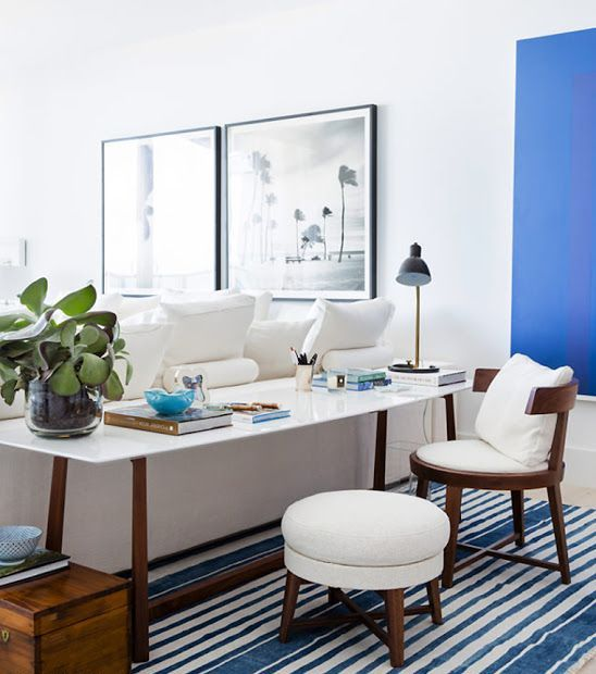 a coastal living room with a bold blue accent wall, creamy furniture, a desk and a chair with a pouf and blue touches