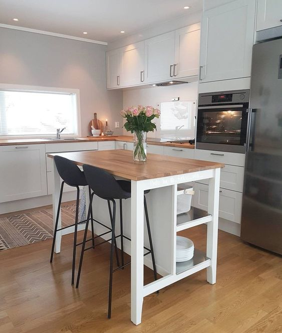 a contemporary white kitchen with butcherblock countertops, a small kitchen island that matches and black stools