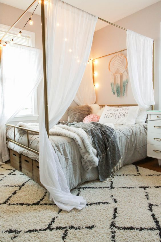 a cozy neutral bedroom with a canopy bed with curtains and lights, neutral bedding, a dream catcher, nightstands and boxes