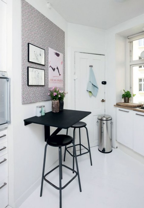 a floating black table with a couple of stools is what you need for a small kitchen, this space can be also used for drinks