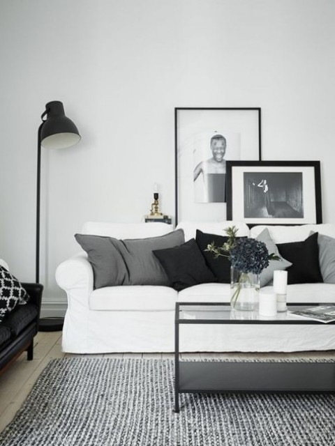 a monochromatic Scandinavian living room with a white Ektorp sofa, contrasting pillows, a low glass table and a gallery wall with monochromatic art