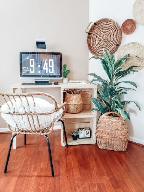 a pretty boho working space with a white desk with crates, a rattan chair, decorative baskets, a potted plant