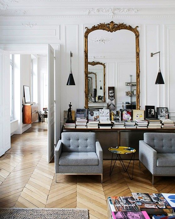 a refined Parisian living room with an oversized mirror in a gilded frame, a table with books and chic furniture