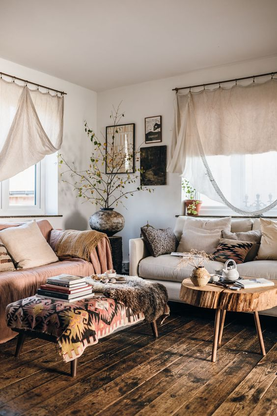 a boho living room with a neutral Stockholm sofa and a blush one, neutral textiles and printed covers plus a tree slice table