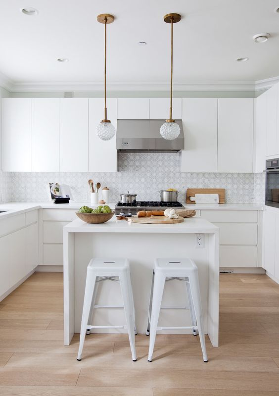a contemporary white kitchen with printed tiles and a small kitchen island, chic pendant lamps and white bar stools