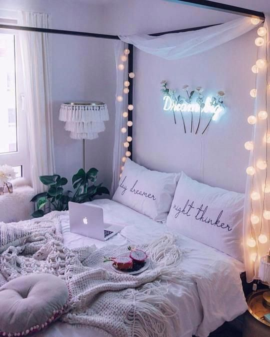 a cozy neutral boho bedroom with a canopy bed styled with lights and neutral fabrics, neutral bedding, a tassel floor lamp and a neon sign
