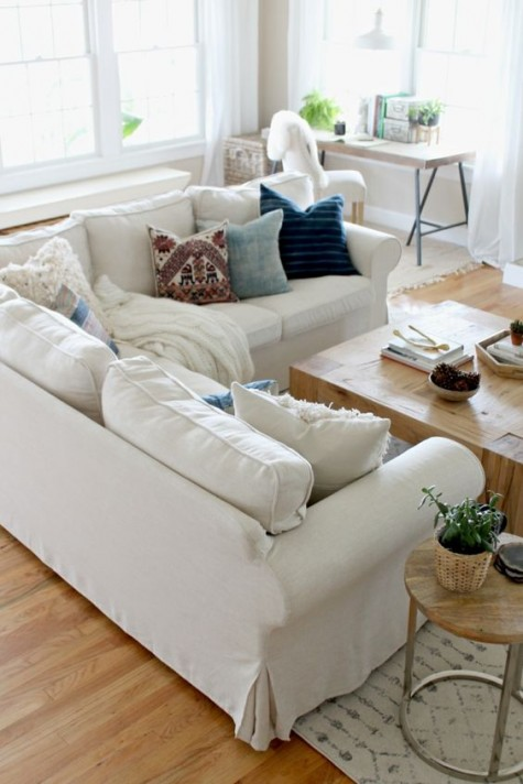 a neutral farmhouse living room with a white Ektorp sectional, a low table, a wooden desk and a side table and potted greenery