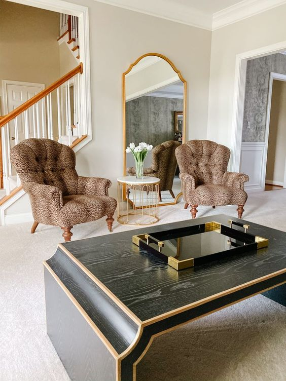 12 a refined living room with a statement mirror in a gilded frame, vintage leopard print chairs, a dark coffee table that echoes with the mirror in its shape