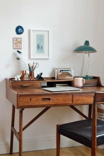 a small and elegant stained vintage desk with drawers, a table lamp and pretty artworks, a black leather chair and feathers