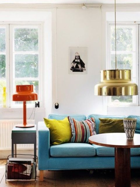 13 a bright living room with a blue Stockholm sofa, retro lamps, colorful pillows and a wooden round table
