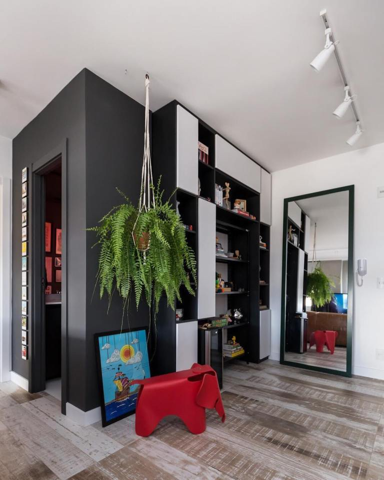 a contemporary black and white space with an oversized mirror in a black frame and open shelves plus potted greenery