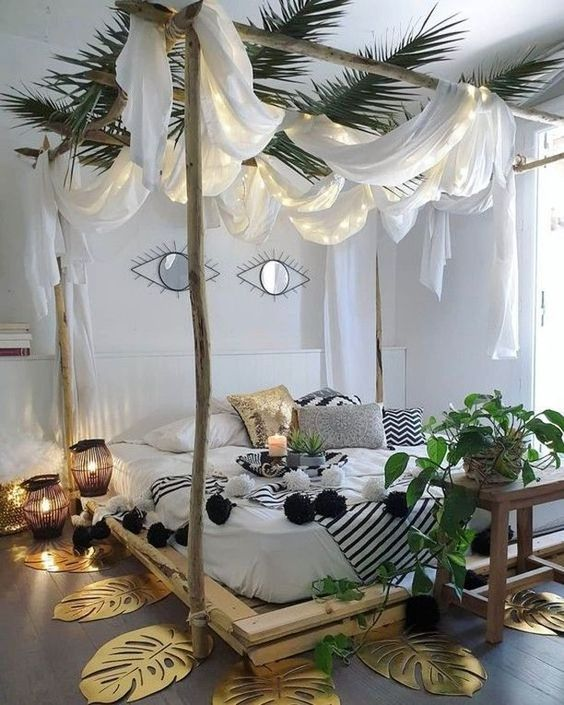 a creative tropical bedroom with a pallet canopy bed with lit up curtains and tropical leaves, gilded monstera leaves on the floor and candle lanterns