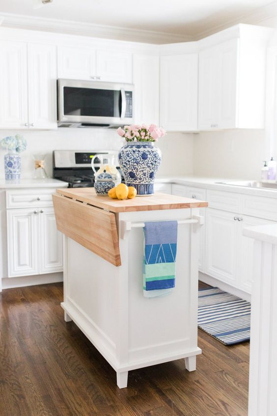 a crispy white kitchen with shaker style cabinetry and a small matching kitchen island wiht a butcherblock countertop for a coastal home