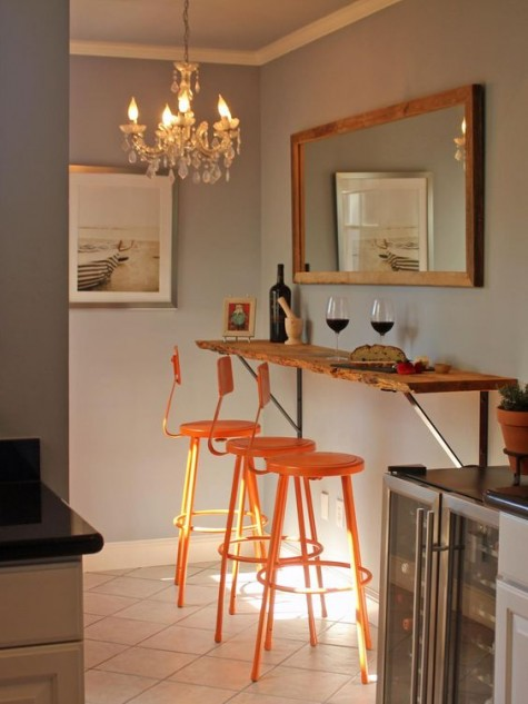 a floating raw edge tabletop plus bright orange stools form a stylish and chic breakfast bar that inspires