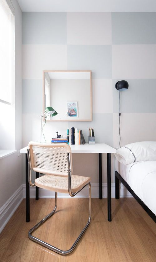 a small and simple desk paired with a cane chair, a couple of lamps can double as a vanity thanks to a mirror on the wall