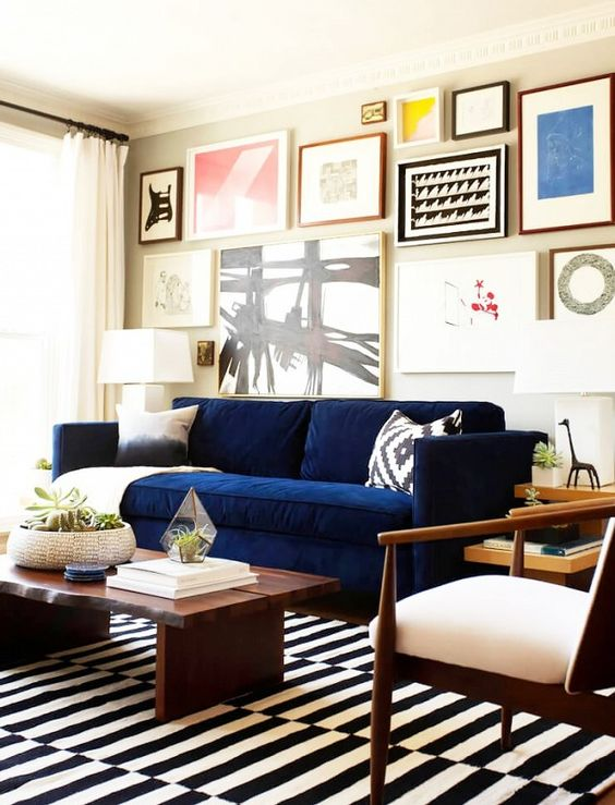 14 a bright living room with a colorful gallery wall, a navy Stockholm sofa, a striped rug and dark furniture