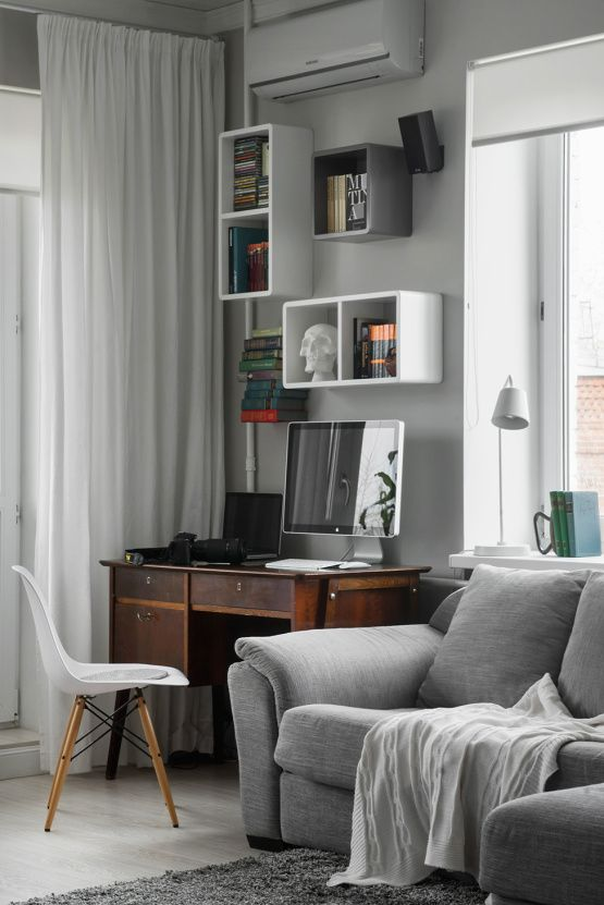 a contemporary grey living room with comfy furniture, a vintage desk and wall-mounted shelves on the wall plus a chair