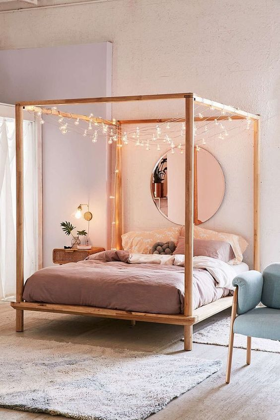 a modern bedroom in pastels, with a canopy bed covered with lights, mauve and pink bedding, a blue chair and a cool nightstand