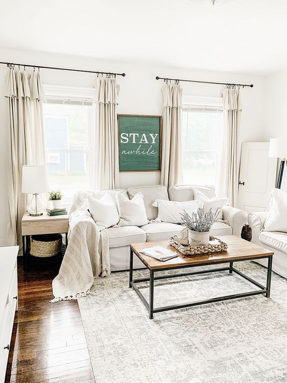 a neutral farmhouse living room with white Ektorp sofas, a wooden table, side tables and floor and table lamps