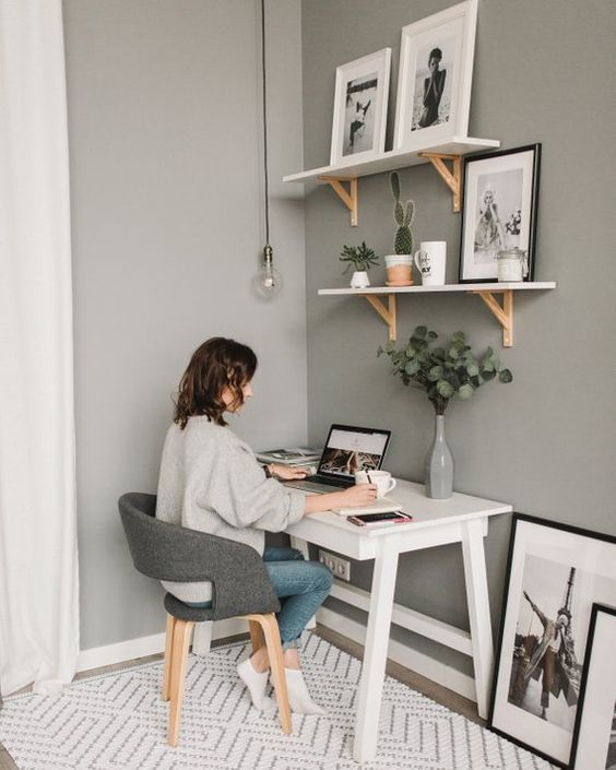 a small and simple white desk, a dupo of shelves over it, a comfy grey chair and potted plants and artworks
