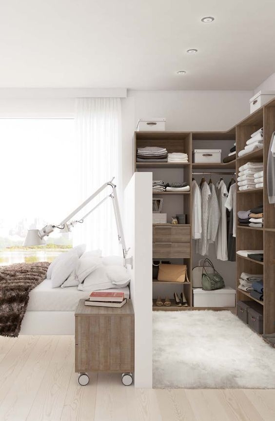 14 a stylish bedroom with a closet incorporated and separated with a pony wall, wall sconces and cool nightstands