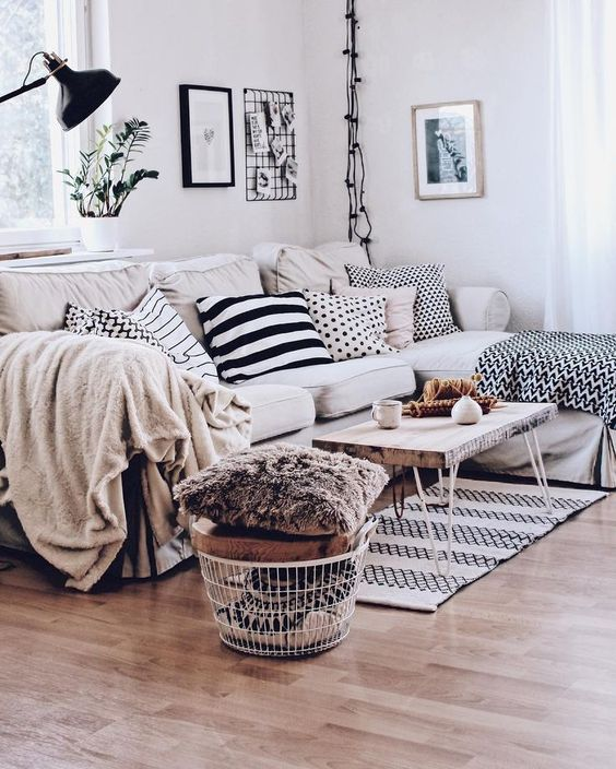 a Scandinavian living room with a sectional Ektorp sofa, printed pillows, a wire basket with pillows and black touches
