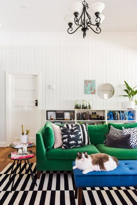 a bright living room with white beadboard walls, an emerald sofa, a blue ottoman, a bookcase and a retro chandelier is chic