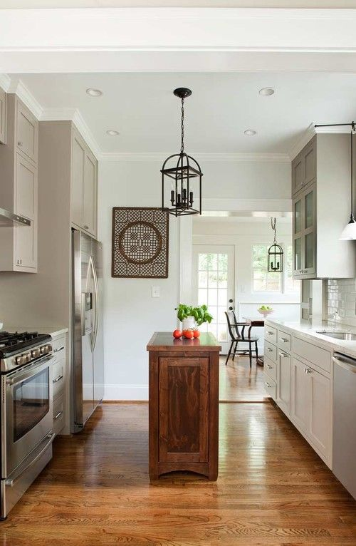 a dove grey kitchen in farmhouse style, with white countertops, a rich-stained wooden kitchen island that contrasts the space