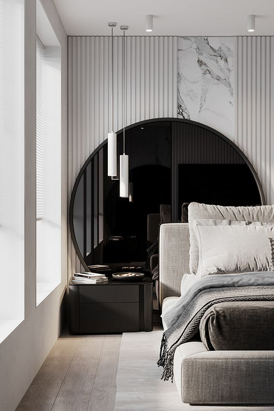 a luxurious bedroom with a dark oversized round mirror, a marble and panel accent wall, an upholstered bed with neutral bedding and pendant lamps