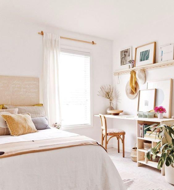 a neutral bedroom with a working space, with a desk, a shelf and a gallery wall plus a potted plant