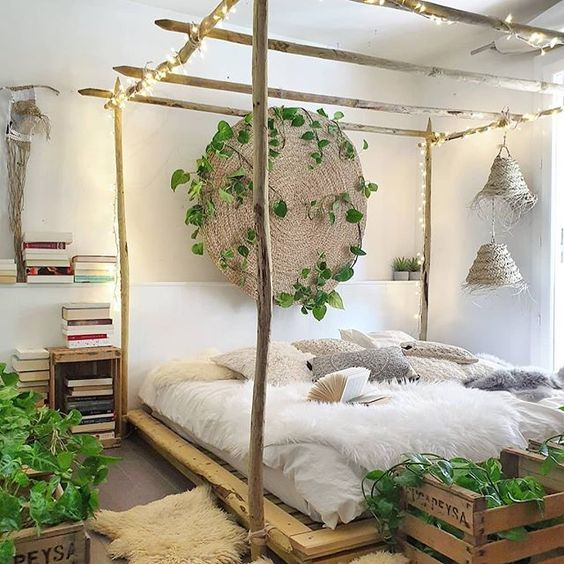 a neutral boho bedroom with a canopy bed with lights, a woven plate with greenery, potted plants and wicker pendant lamps