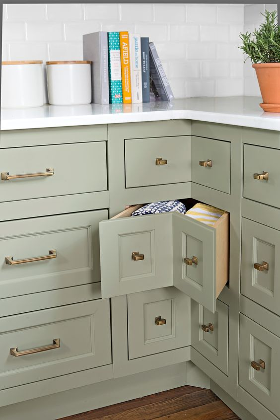 an olive green farmhouse kitchen with shaker style cabinets and corner drawers with brass knobs