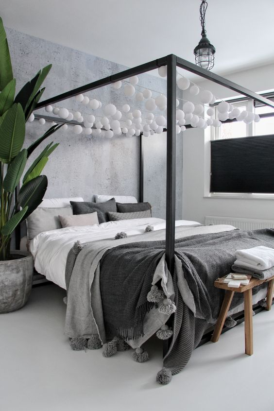 a Scandinavian bedroom in greys, with a canopy bed styled with lights over it, grey bedding, a bench and a statement plant